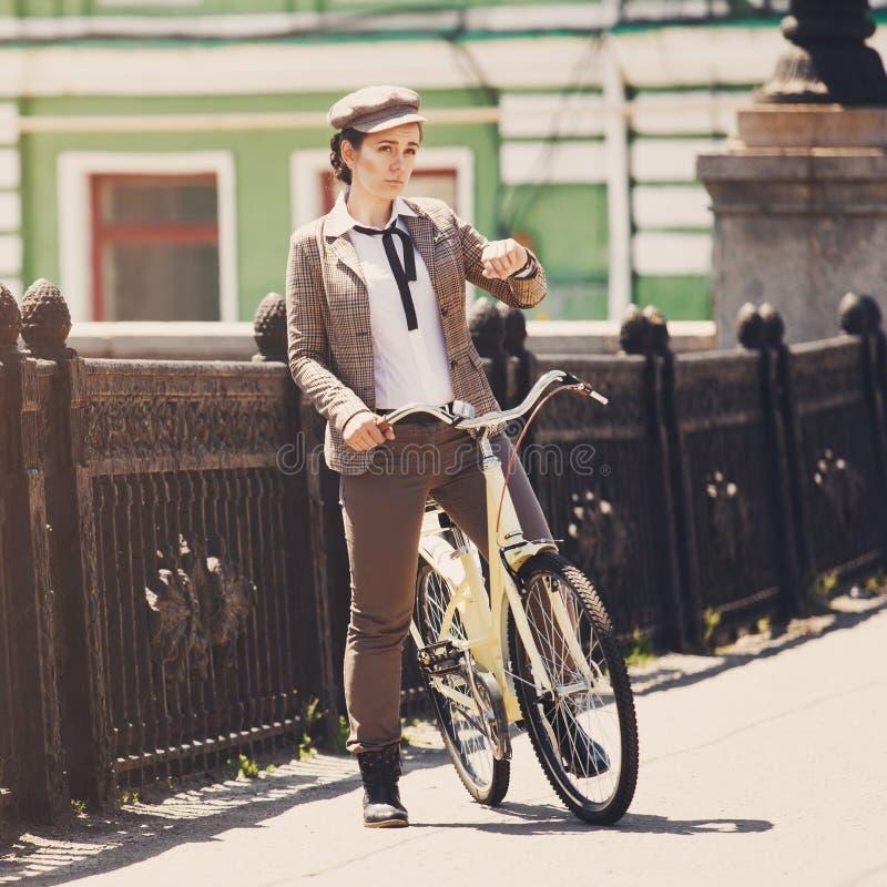 Giovane donna a stile d'annata di britannici della bicicletta fotografia stock libera da diritti