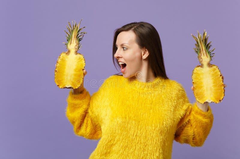 Giovane donna stupita che guarda da parte tenente i halfs aperti della tenuta della bocca della frutta matura fresca dell'ananas  immagini stock libere da diritti