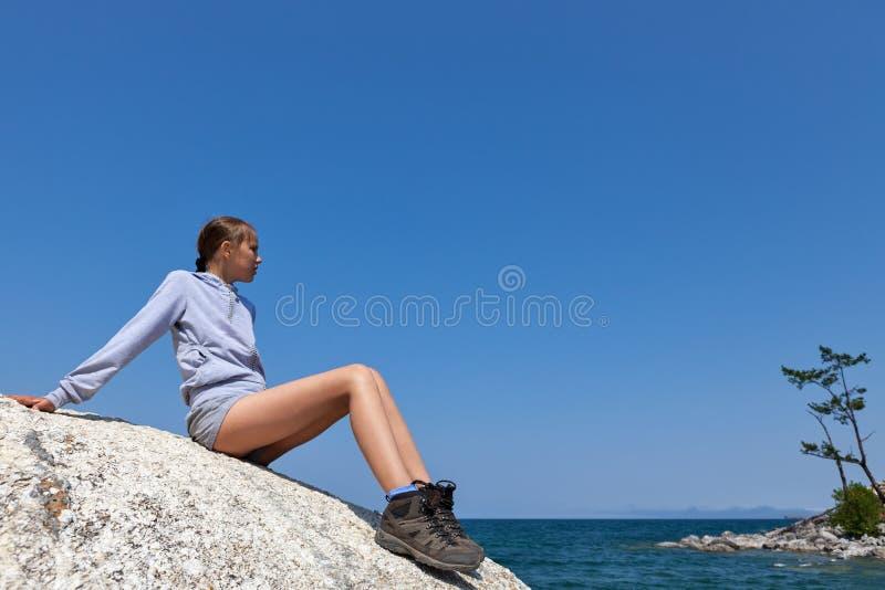 Giovane donna su grande roccia contro cielo blu immagine stock