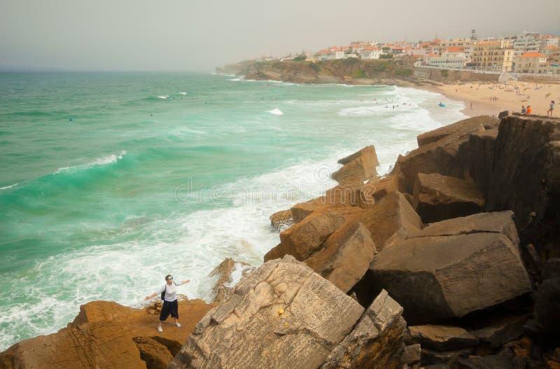 Giovane donna su una grande pietra di Praia das Macas Sintra, Portogallo immagini stock