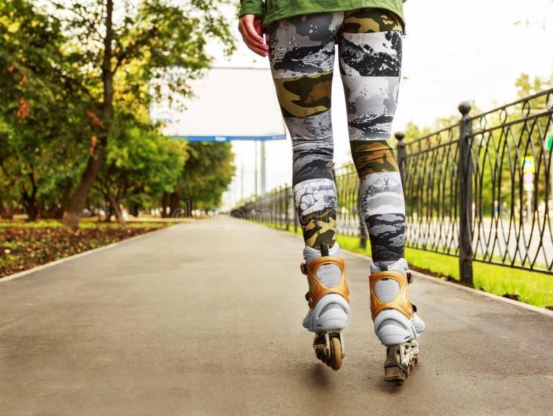 Giovane donna sui pattini di rullo nel parco immagini stock