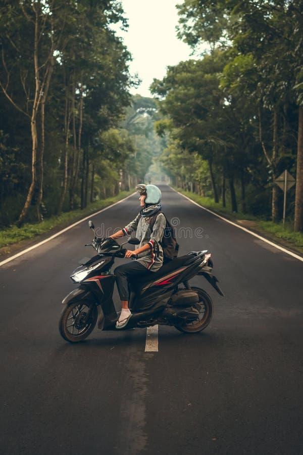 Giovane donna sul motorino sulla strada fra gli alberi Isola di Bali immagine stock