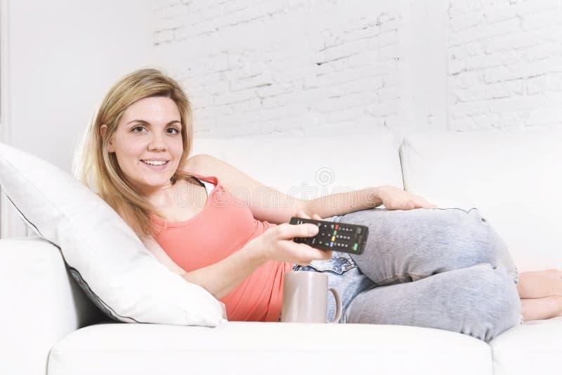 Giovane donna sul regolatore a distanza della televisione della tenuta del sofà che guarda sorridere della TV felice fotografia stock