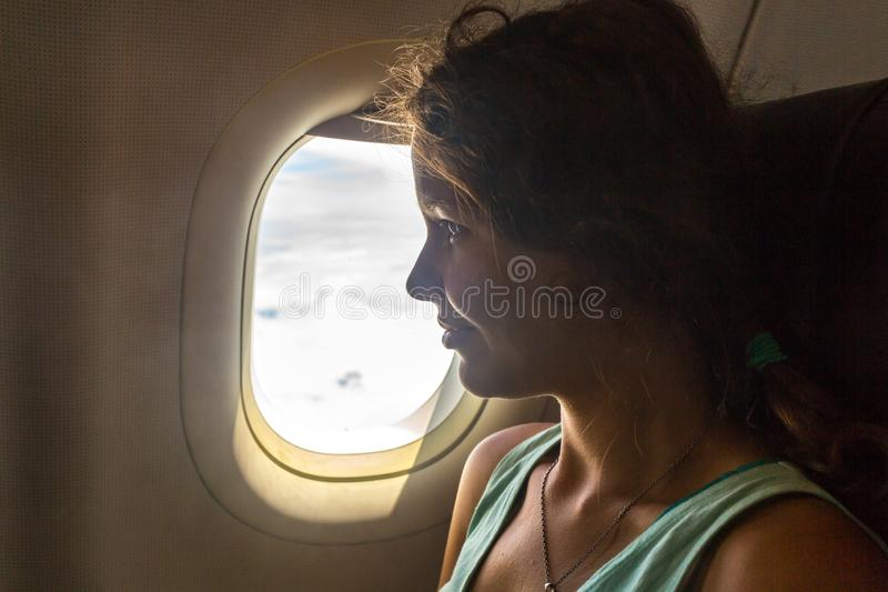 Giovane donna sul sedile del passeggero vicino alla finestra in aeroplano fotografie stock libere da diritti