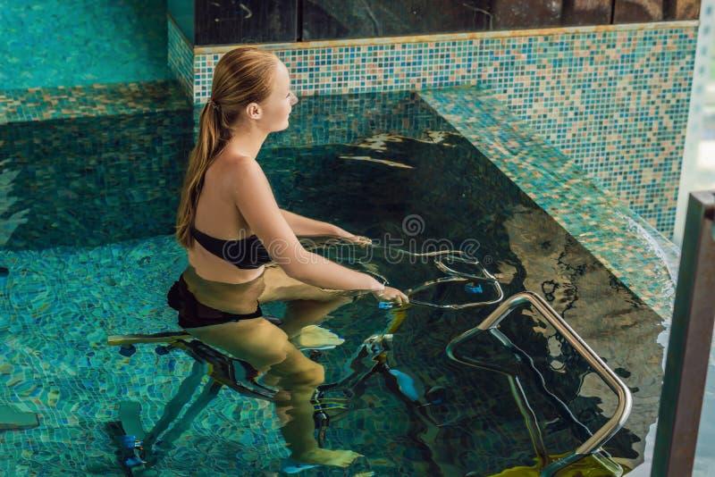 Giovane donna sul simulatore della bicicletta subacqueo nello stagno fotografia stock libera da diritti