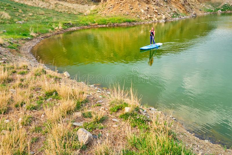 Giovane donna sul SUP del bordo di pagaia nel lago Iacobdeal, Romania, remante vicino al litorale, sulle acque tranquille e incon fotografia stock libera da diritti