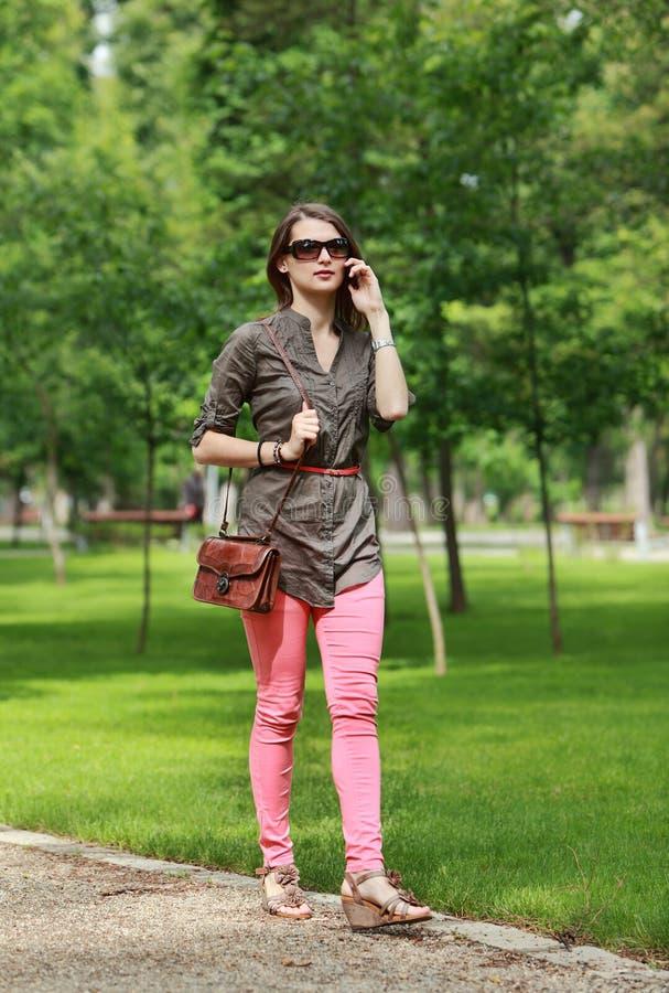 Giovane donna sul telefono che cammina in un parco fotografie stock