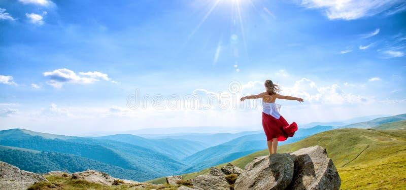 Giovane donna sulla cima della montagna immagini stock