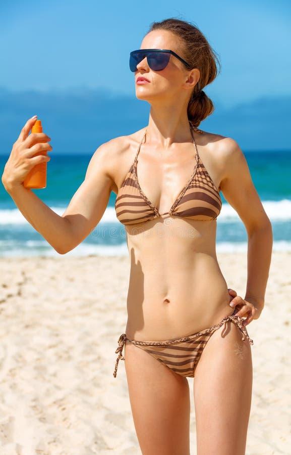 Giovane donna sulla spiaggia che applica lozione solare fotografia stock