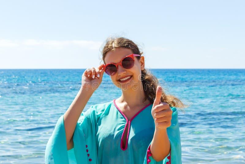 Giovane donna sulla spiaggia che dà i pollici sul giorno soleggiato fotografia stock libera da diritti