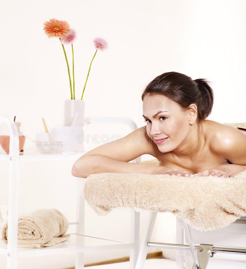 Giovane donna sulla tabella di massaggio nella stazione termale di bellezza. immagini stock libere da diritti