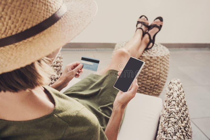 Giovane donna sulle vacanze facendo uso del telefono e della carta di credito Concetto online di acquisto fotografie stock