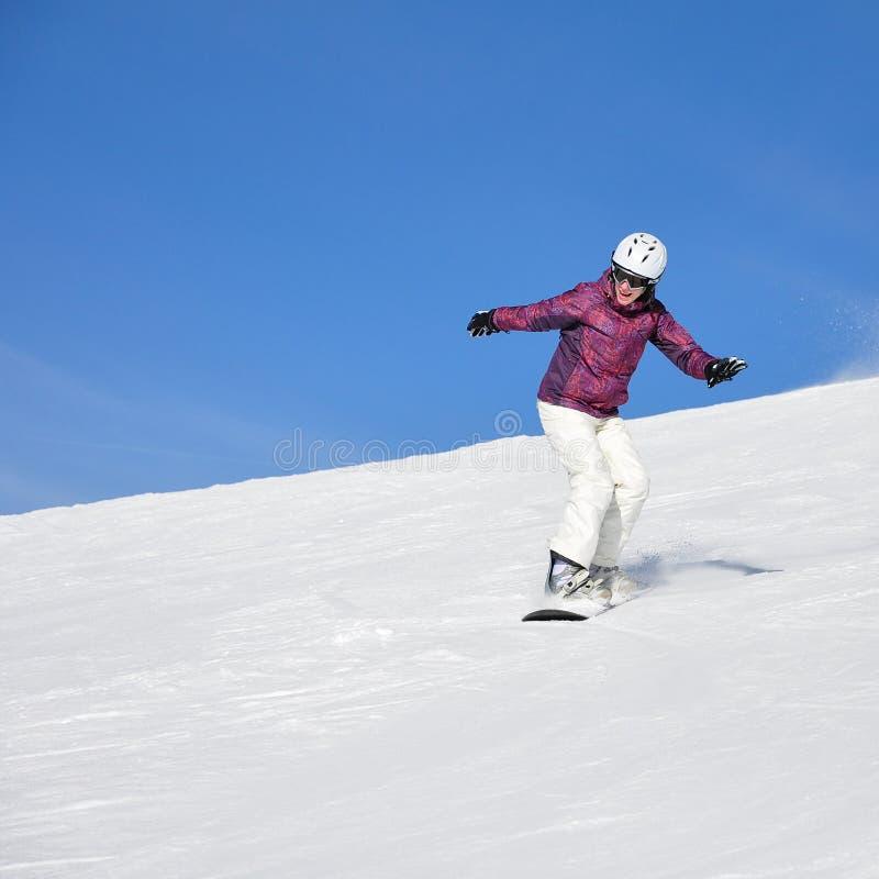 Giovane donna sullo snowboard fotografia stock