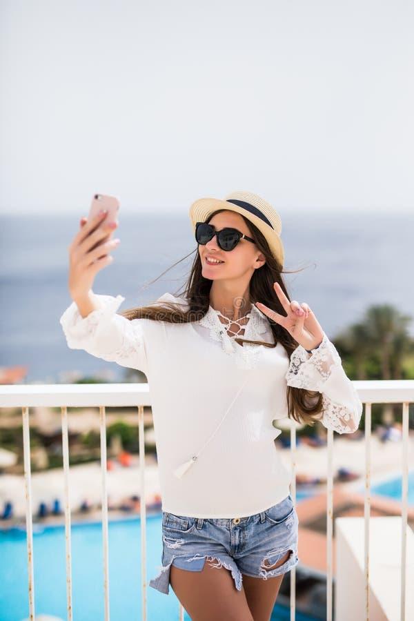 Giovane donna sveglia che fa selfie sulla spiaggia dell'oceano, sull'attrezzatura d'uso di boho e sugli occhiali da sole diverten fotografia stock
