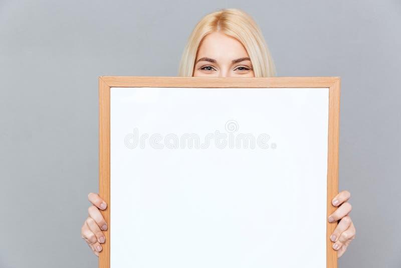 Giovane donna sveglia che nasconde il suo fronte dietro il bordo bianco in bianco immagini stock libere da diritti