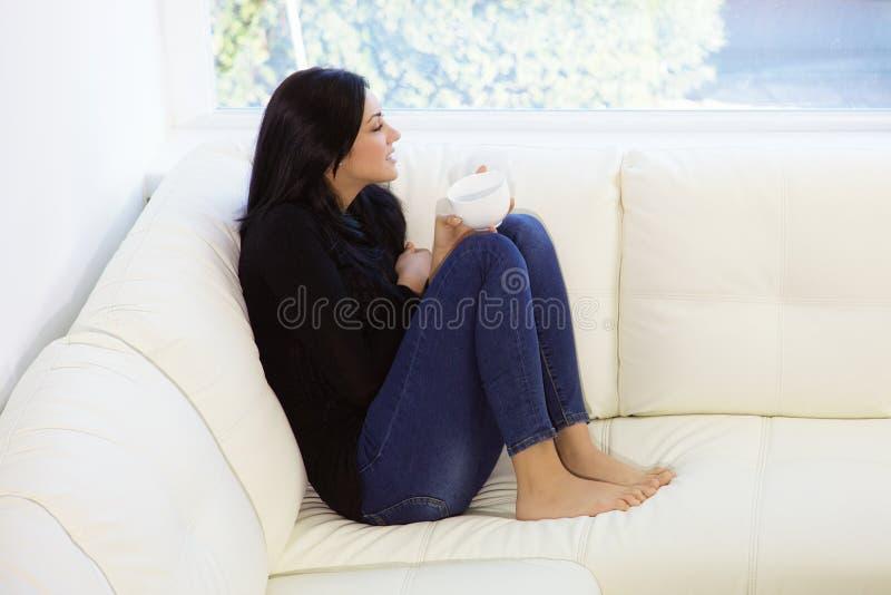 Giovane donna sveglia che si rilassa sul caffè bevente del sofà immagini stock libere da diritti
