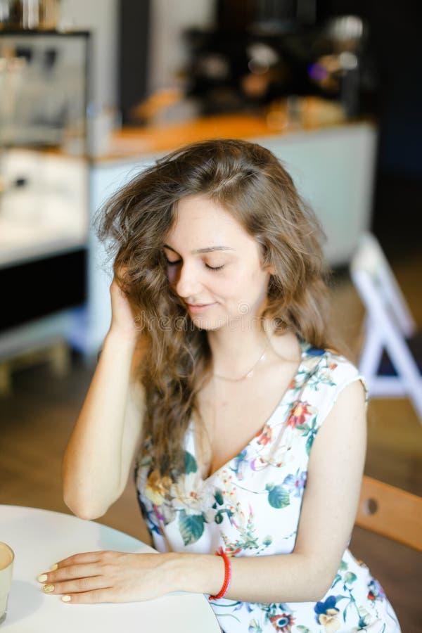 Giovane donna sveglia che si siede al caffè e che tocca capelli ricci fotografia stock