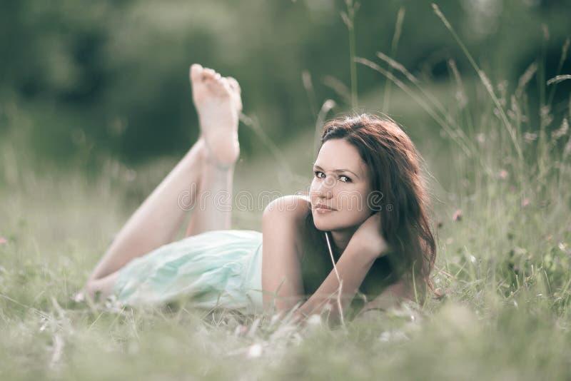 Giovane donna sveglia che si trova in una radura della foresta immagini stock