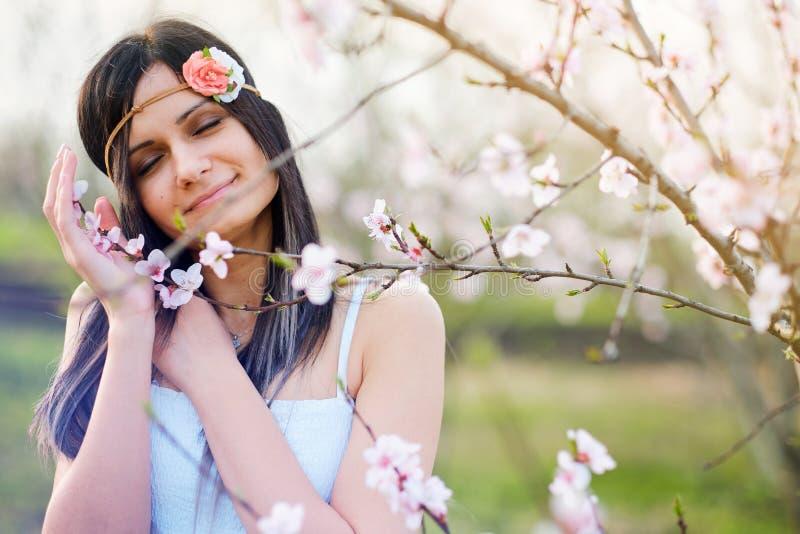 Giovane donna sveglia con l'albero di fioritura fotografie stock libere da diritti