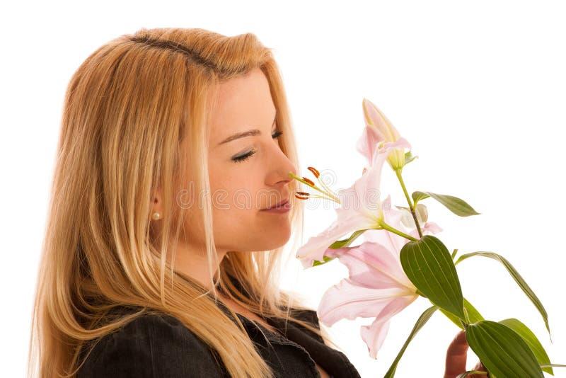 Giovane donna sveglia con uno studio rosa del giglio isolato sopra bianco immagini stock libere da diritti