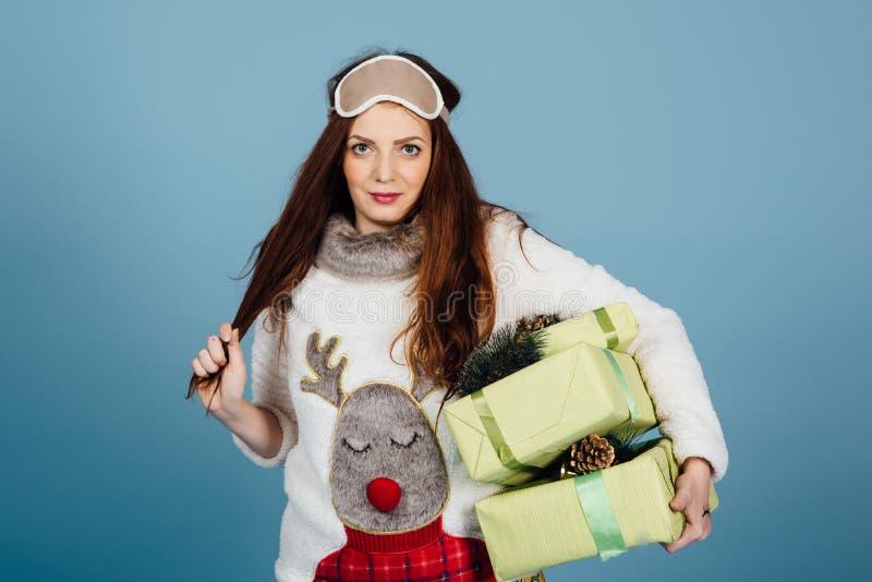 Giovane donna sveglia in pigiami che stanno con le scatole del regalo di Natale e che si divertono sul fondo blu fotografia stock libera da diritti