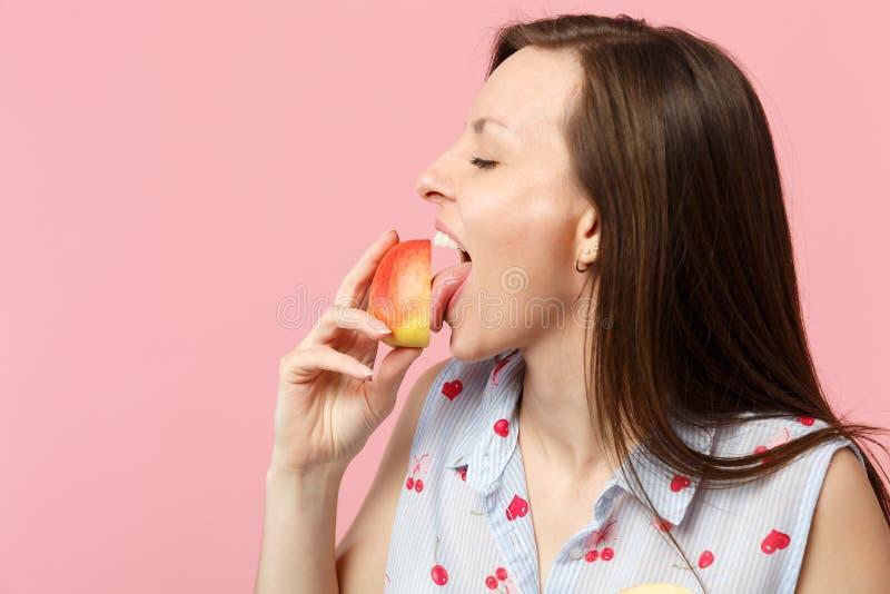 Giovane donna sveglia in vestiti di estate che tengono leccatura a metà della frutta matura fresca della mela isolata sulla paret fotografie stock libere da diritti