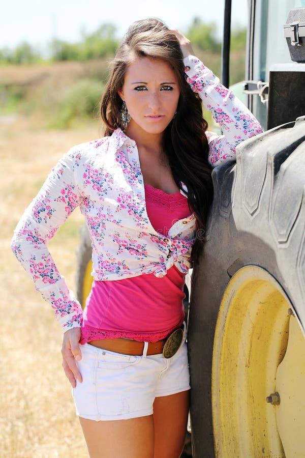 Giovane donna teenager all'aperto vicino al trattore immagini stock