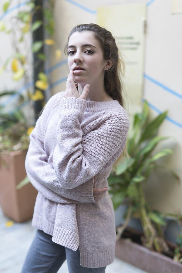 Giovane donna teenager con la mano sul suo fronte che esamina la macchina fotografica immagini stock