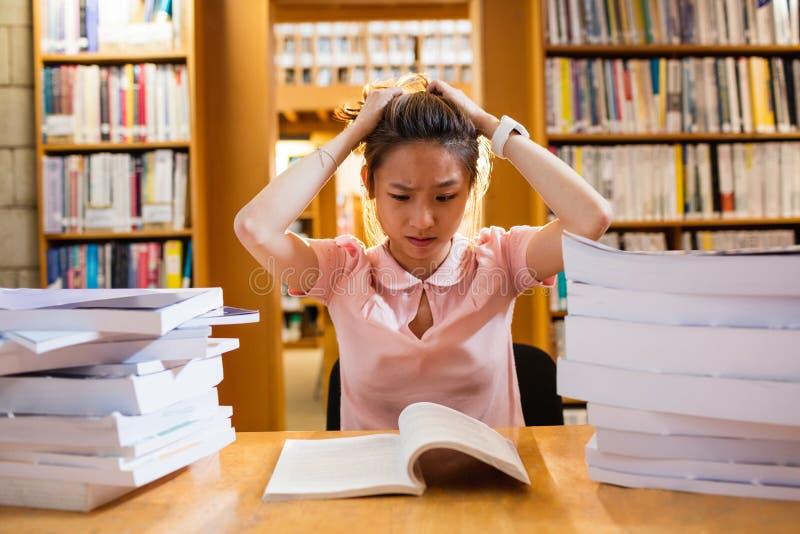 Giovane donna tesa che studia nella biblioteca immagini stock libere da diritti