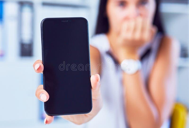 Giovane donna triste che mostra uno schermo in bianco dello smartphone Fuoco sullo smartphone Spazio libero per il vostro messagg immagine stock