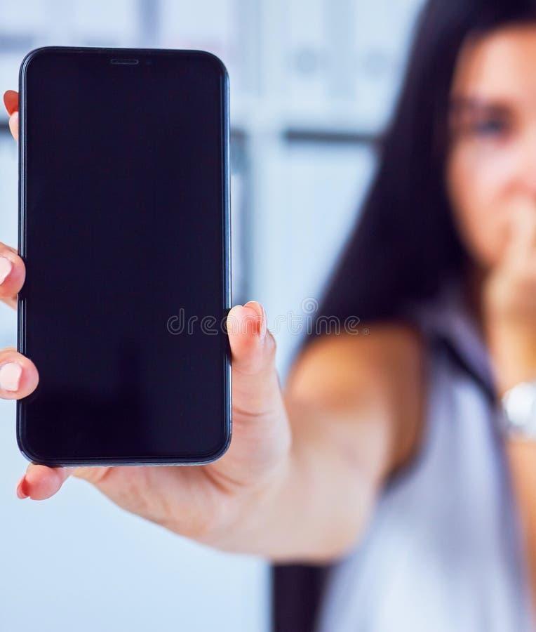Giovane donna triste che mostra uno schermo in bianco dello smartphone Fuoco sullo smartphone Spazio libero per il vostro messagg fotografie stock