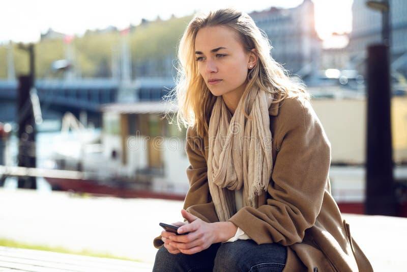 Giovane donna triste che pensa ai suoi problemi mentre sedendosi accanto al fiume nella citt? fotografia stock