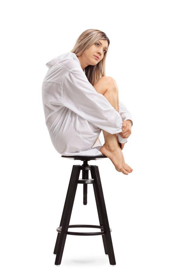 Giovane donna triste che si siede su una sedia fotografia stock