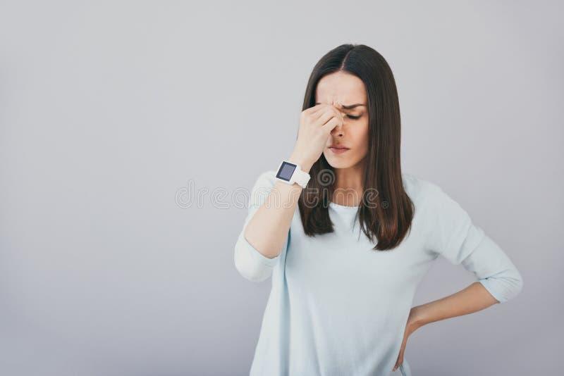 Giovane donna triste che sta contro il fondo bianco fotografia stock libera da diritti