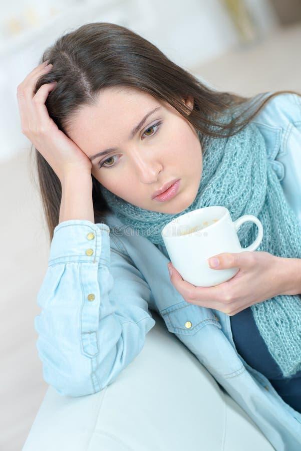 Giovane donna triste con il caffè o il tè della tazza fotografie stock libere da diritti