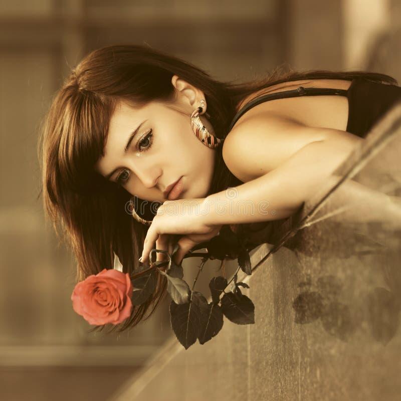 Giovane donna triste con la rosa rossa sulla via della città immagine stock libera da diritti