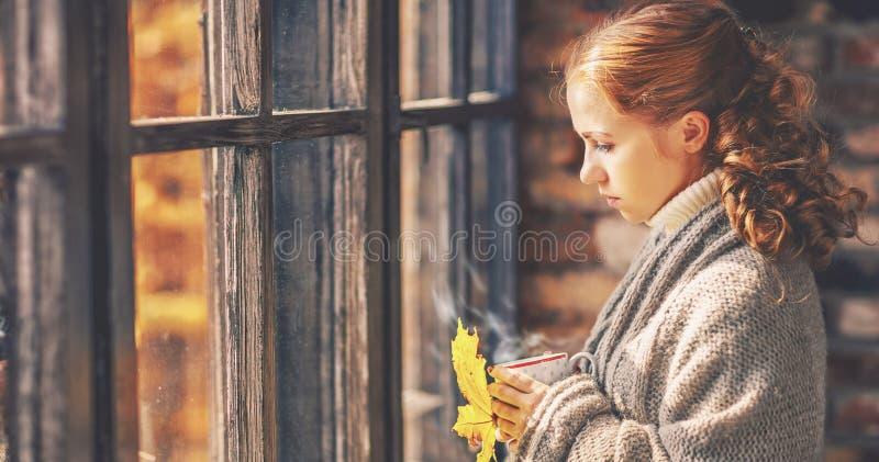 Giovane donna triste con la tazza di caffè calda nella finestra di autunno fotografie stock libere da diritti