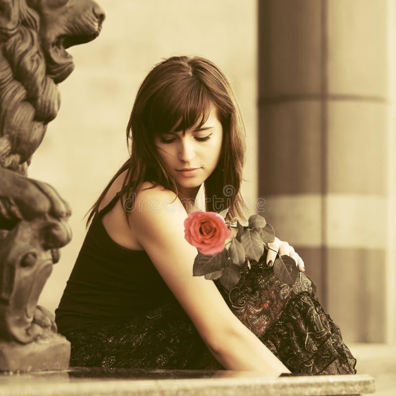 Giovane donna triste con una rosa rossa all'aperto fotografia stock