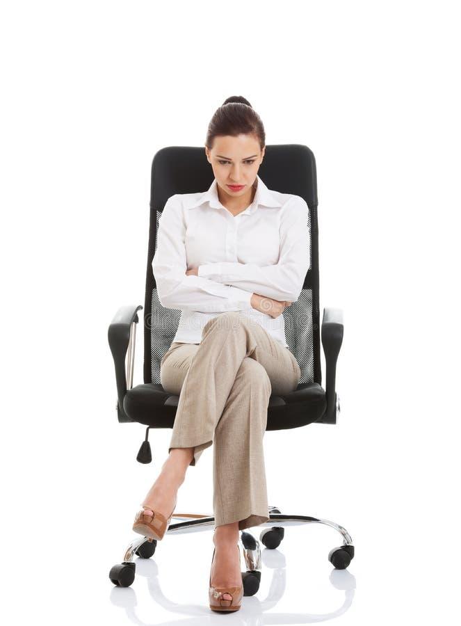 Giovane donna triste di affari che si siede su una sedia. fotografie stock libere da diritti