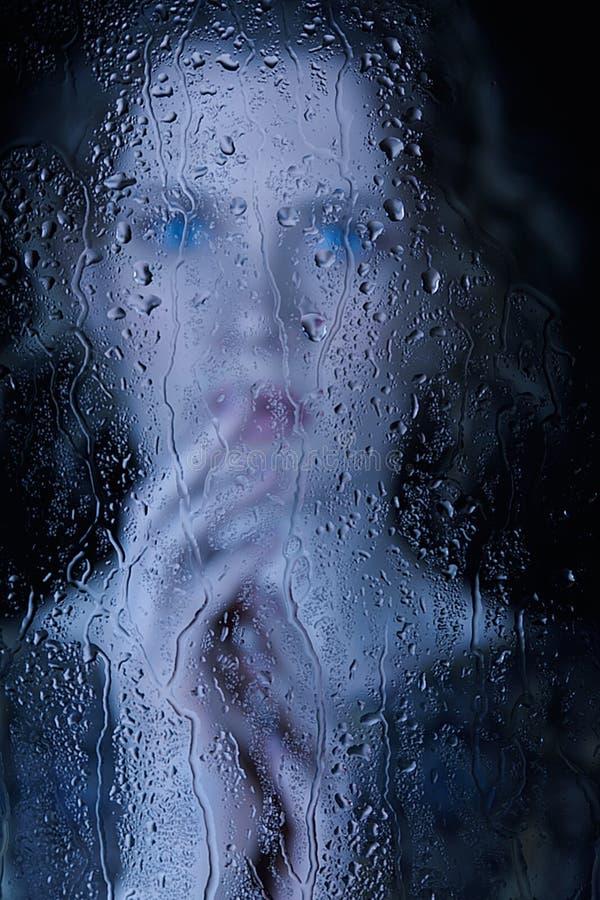 Giovane donna triste dietro il vetro di finestra con le gocce di pioggia fotografia stock