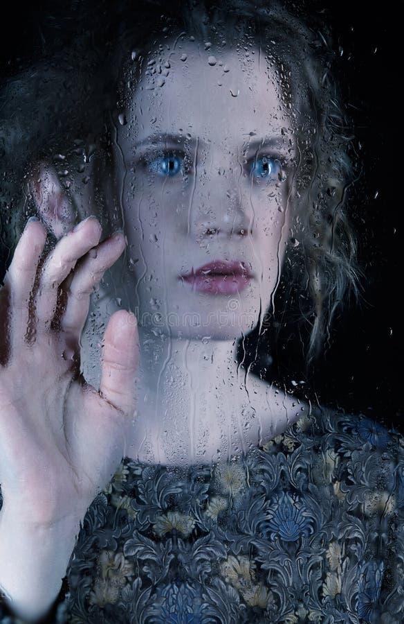 Giovane donna triste dietro il vetro di finestra con le gocce di pioggia fotografia stock libera da diritti