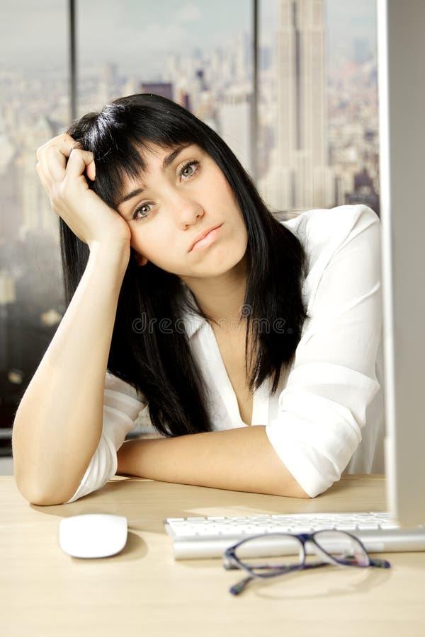 Giovane donna triste e annoiata di affari in ufficio a New York fotografia stock libera da diritti