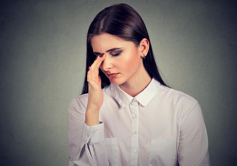 Giovane donna triste sollecitata in una situazione disperata che guarda giù fotografia stock libera da diritti