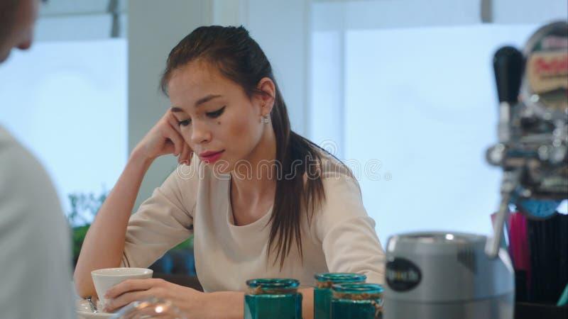 Giovane donna turbata che sporge querela al barista al contatore della barra in caffè stock footage