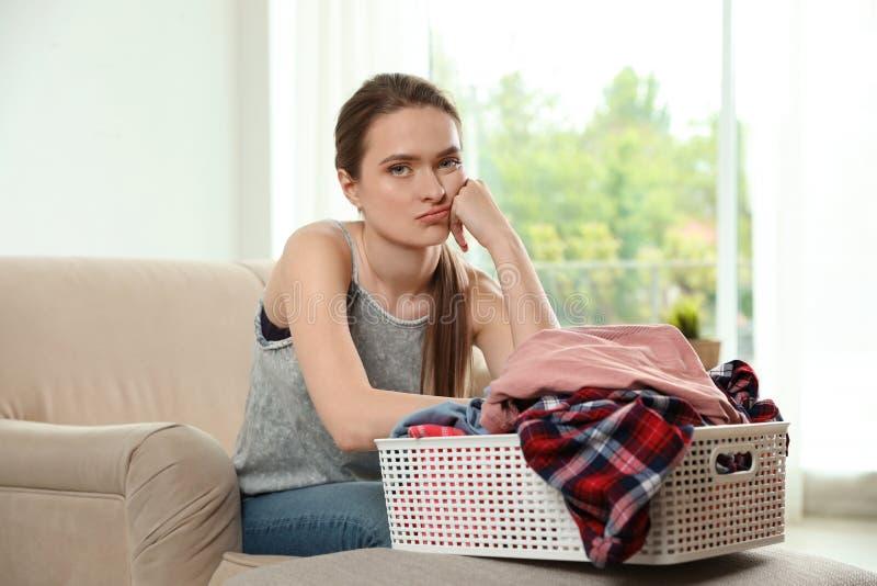 Giovane donna turbata con il canestro della lavanderia pulita sul sofà fotografia stock libera da diritti