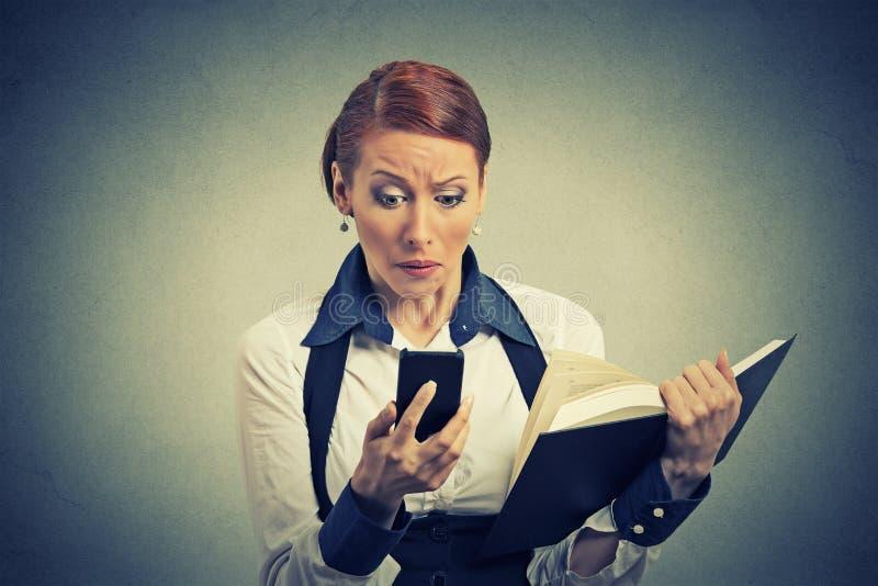 Giovane donna turbata di affari che esamina telefono che vede il libro della tenuta di cattive notizie fotografia stock