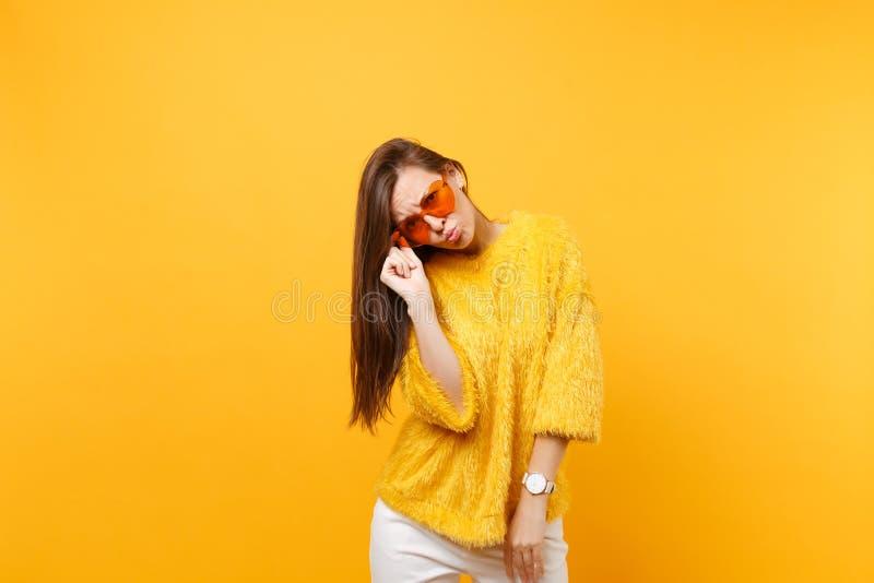 Giovane donna turbata graziosa in maglione della pelliccia e pantaloni bianchi che tengono i vetri arancio del cuore, labbra di s immagini stock libere da diritti