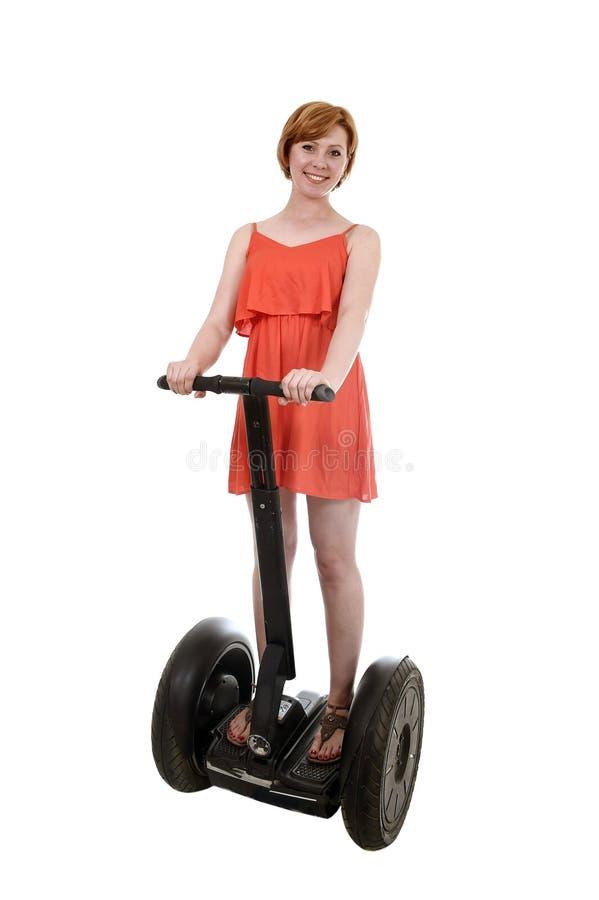 Giovane donna turistica attraente in segway elettrico sorridente di guida felice del vestito elegante da estate immagine stock libera da diritti