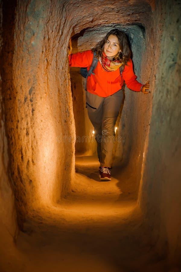Giovane donna turistica esplorare la città sotterranea antica della caverna di Derinkuyu fotografie stock libere da diritti