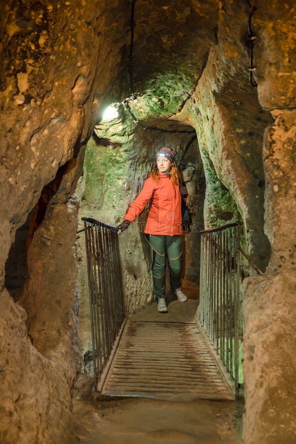 Giovane donna turistica esplorare la città sotterranea antica della caverna di Kaymakli fotografia stock libera da diritti